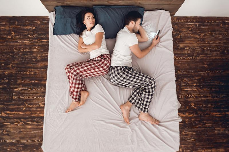 Opinião do reboque O homem considerável adulto com o telefone nas mãos impede dormir ao lado da jovem mulher de encontro imagens de stock royalty free