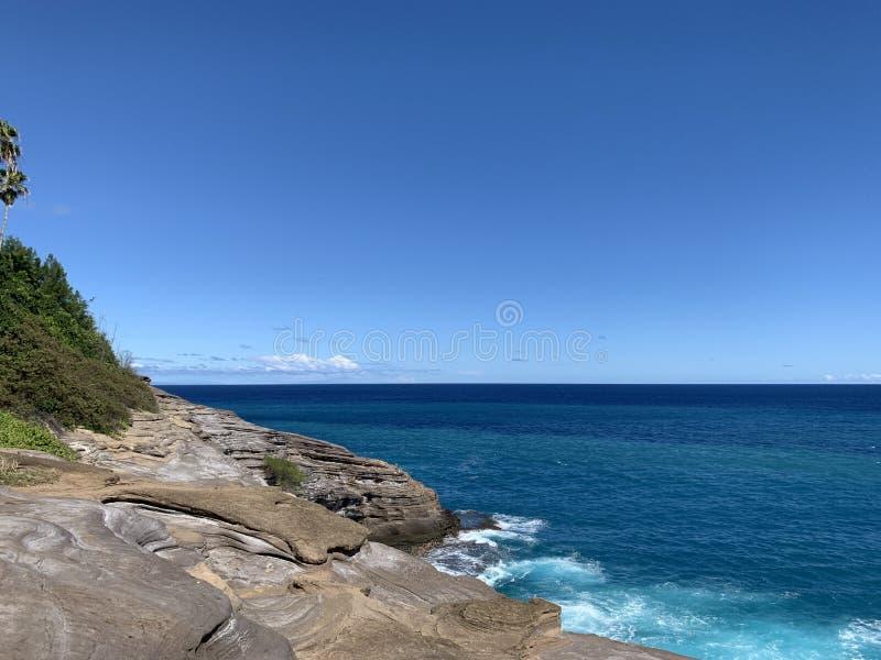 Opinião do retrato da caverna cuspir de Havaí da rocha e do céu imagem de stock royalty free