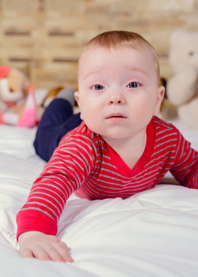 Opinião do retrato do close up um bebê pequeno bonito de sorriso engraçado com o cabelo louro que encontra-se na cama com a cober fotos de stock royalty free