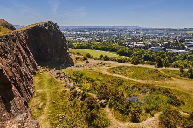 Opinião do verão de penhascos de Salisbory no parque de Holyrood perto do ` s Seat de Arthur com grama verde bonita e o céu azul  fotografia de stock