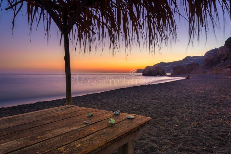 Opinião do verão de uma praia no por do sol com pedras em uma tabela, Tertsa, Creta fotos de stock
