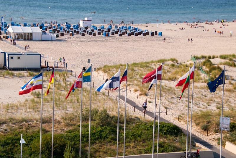 Opinião do zangão da praia bonita em Warnemunde, Alemanha em cabanas, em banhistas e em bandeiras da praia do mar Báltico foto de stock