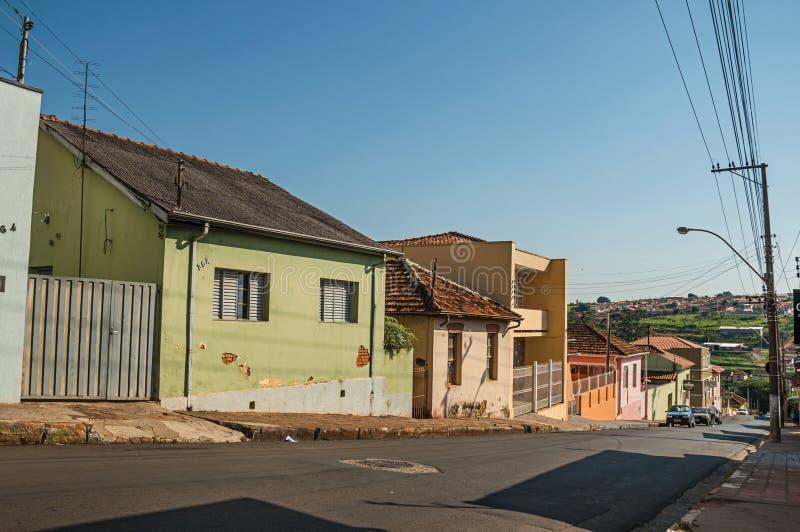 Opinião em declive da rua com paredes do passeio e as casas coloridas em um dia ensolarado em São Manuel fotografia de stock