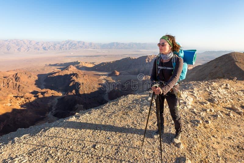 Opinião ereta da garganta da borda da montanha do deserto da jovem mulher do mochileiro fotografia de stock