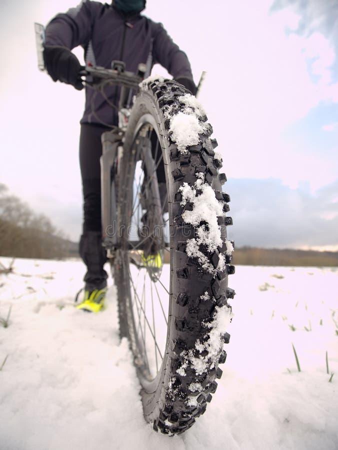 Opinião extrema do fim do baixo ângulo à bicicleta da montanha obstruída na fuga gelada nevado Vista larga extrema imagens de stock
