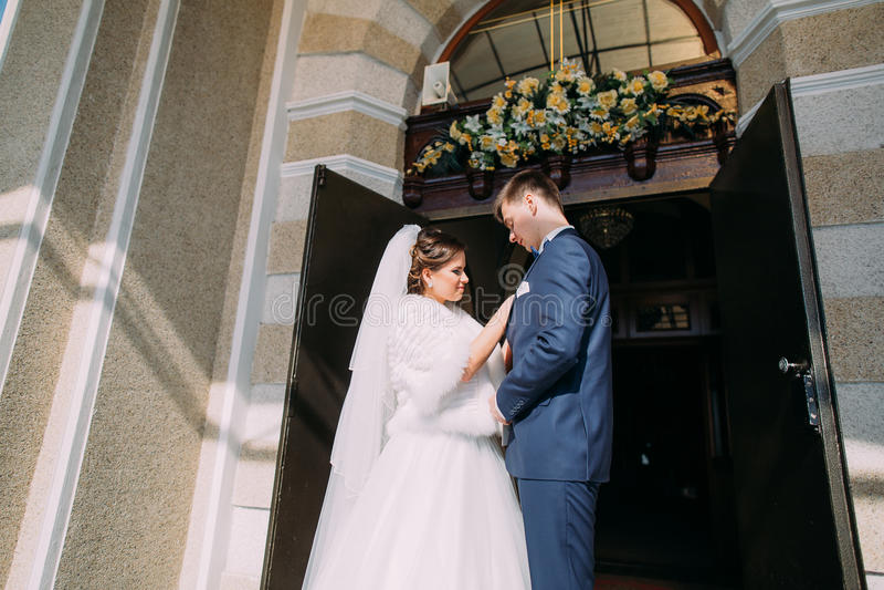 A opinião horizontal os recém-casados felizes que estão perto da igreja imagem de stock royalty free