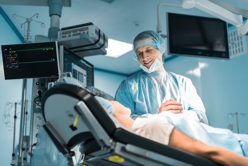 opinião inferior o doutor e o paciente de sorriso que guardam as mãos foto de stock