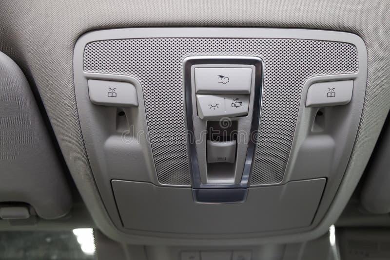 A opinião interior do close-up com os botões do painel e do teto-solar do controle de luz do telhado do suv branco novo caro mesm fotografia de stock