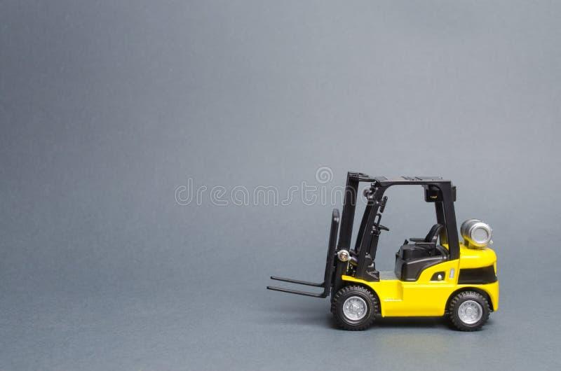 Opinião lateral amarela de caminhão de empilhadeira no fundo cinzento Equipamento do armazém, veículo Descarregamento, transporte imagens de stock royalty free