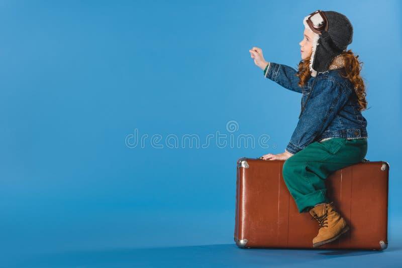 opinião lateral a criança adorável do preteen no traje piloto que senta-se na mala de viagem imagens de stock