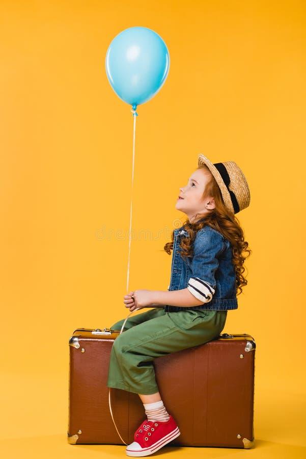 opinião lateral a criança com o balão que senta-se na mala de viagem fotografia de stock