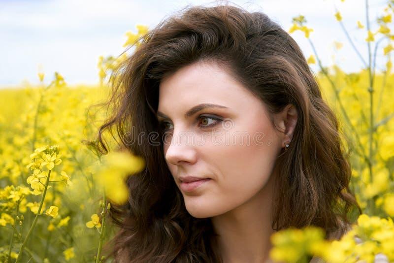Opinião lateral do close up da cara da menina, flor amarela no fundo, estação de mola, campo da colza e céu fotografia de stock