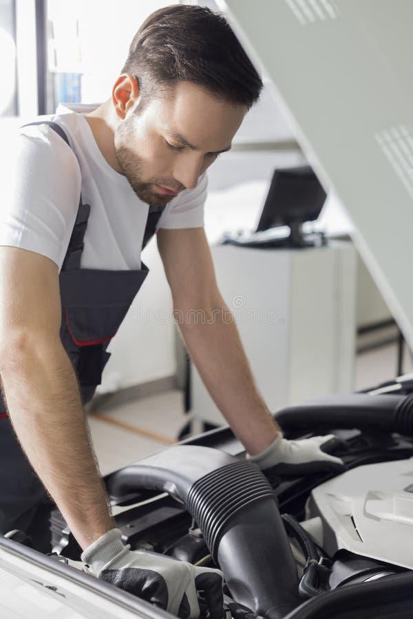 Opinião lateral do comprimento completo do motor de automóveis de exame do mecânico masculino na oficina de reparações foto de stock royalty free