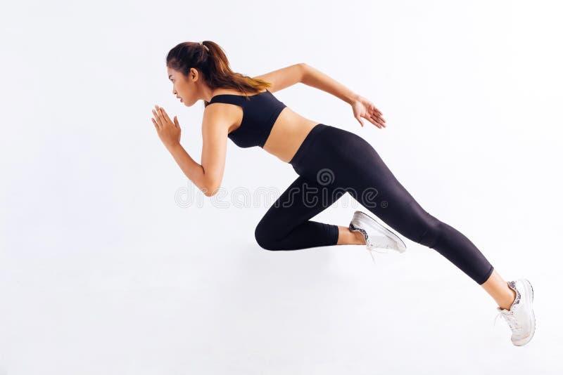 Opinião lateral a fêmea asiática magro no sportswear preto que corre rapidamente durante o exercício no fundo branco imagem de stock