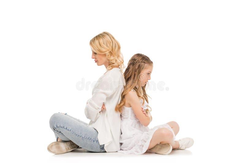 opinião lateral a filha e a mãe da virada que sentam-se de volta à parte traseira fotografia de stock royalty free