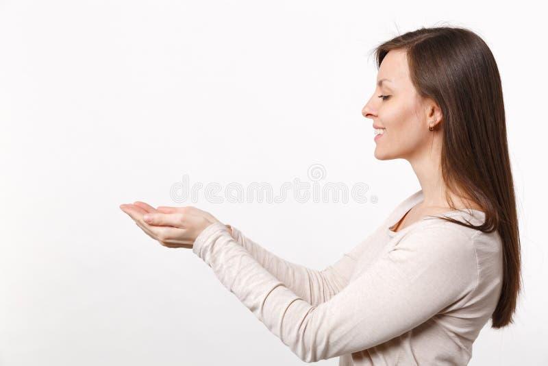 Opinião lateral a jovem mulher bonita de sorriso na roupa leve que está guardando algo nas mãos isoladas na parede branca fotografia de stock