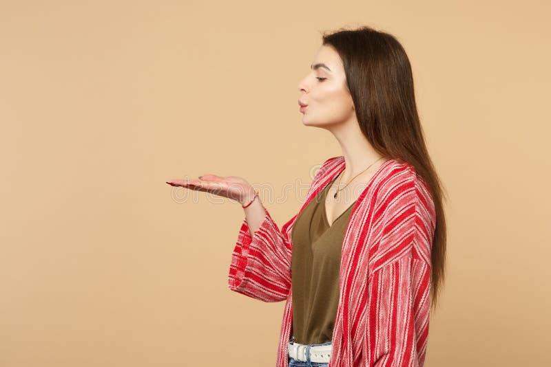 Opinião lateral a jovem mulher bonito bonita na roupa ocasional que funde enviando o beijo do ar isolada na parede bege pastel imagem de stock royalty free