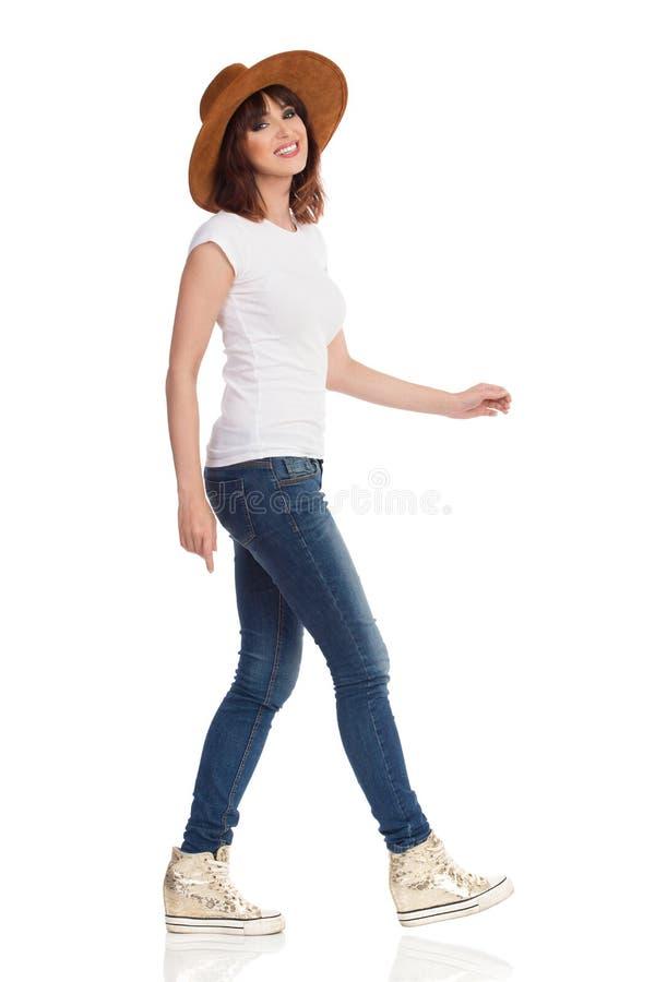 Opinião lateral a jovem mulher de passeio de sorriso no t-shirt e no chapéu brancos fotografia de stock royalty free