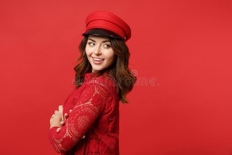 A opinião lateral a jovem mulher de sorriso no vestido do laço, mão da terra arrendada do tampão cruzou a vista de lado na parede fotografia de stock