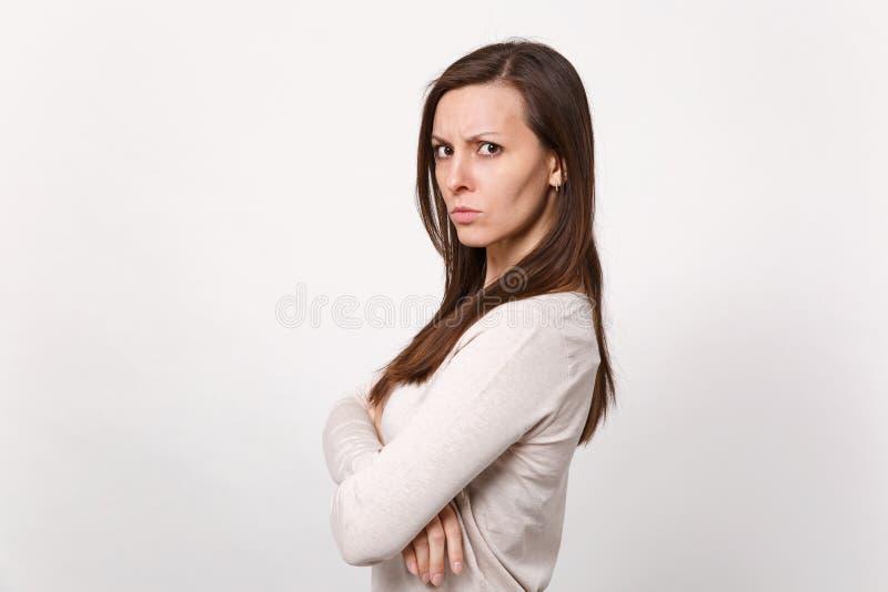 Opinião lateral a jovem mulher descontentada irritada na roupa leve que olha a câmera, mantendo as mãos dobradas isoladas na pare fotografia de stock