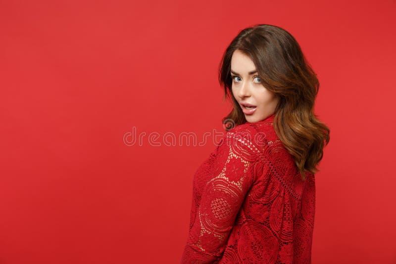 Opinião lateral a jovem mulher entusiasmado atrativa na posição do vestido do laço que olha a câmera isolada no fundo vermelho br imagens de stock royalty free