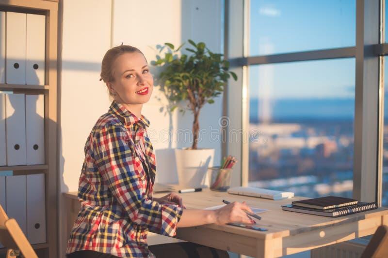 Opinião lateral a jovem mulher feliz que trabalha no escritório domiciliário, escrevendo no papel Material de aprendizagem do est foto de stock royalty free