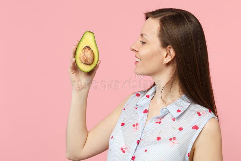 Opinião lateral a jovem mulher na roupa do verão que mantém o fruto de abacate verde maduro fresco isolado na parede pastel cor-d fotografia de stock royalty free
