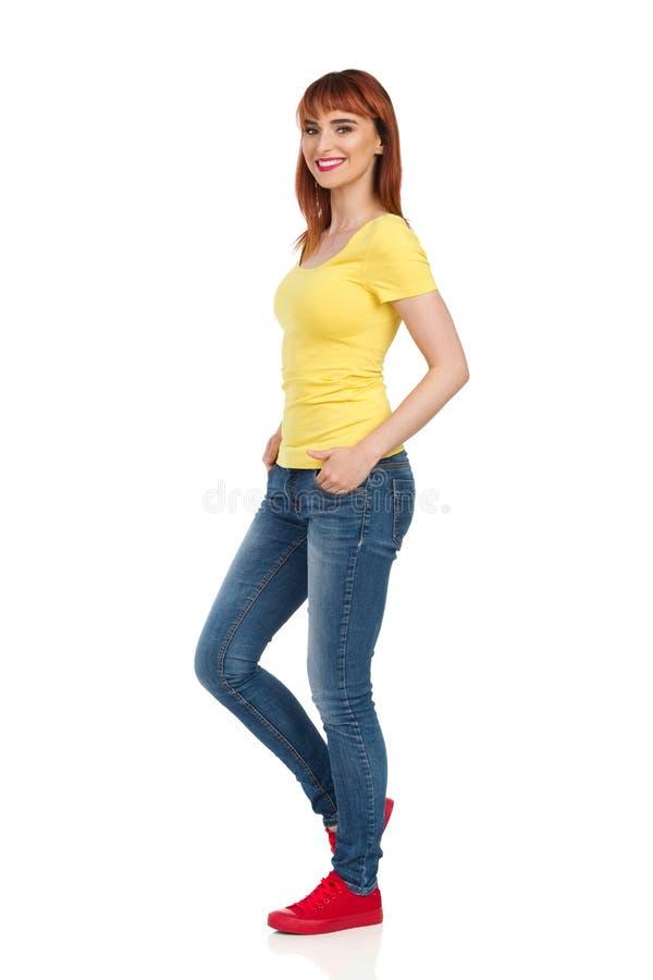 Opinião lateral a jovem mulher ocasional de sorriso que está com mãos no bolso e que olha a câmera fotos de stock