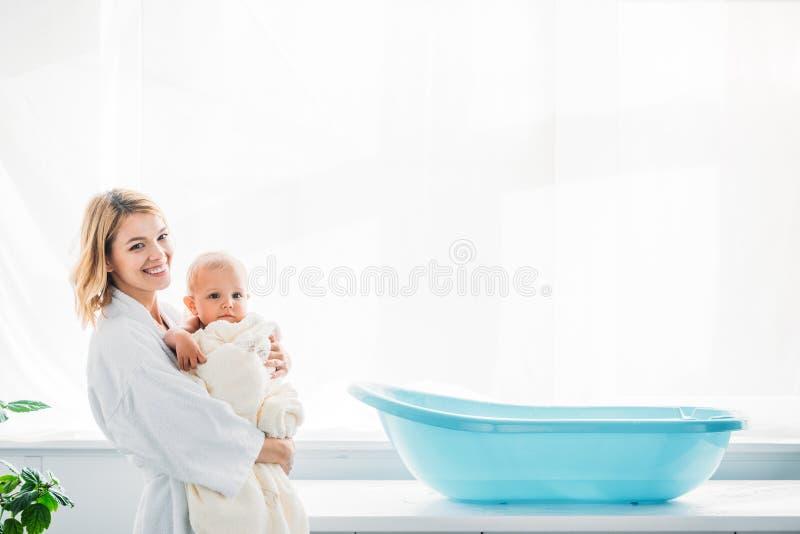 opinião lateral a mãe feliz no roupão que leva a criança adorável fotografia de stock royalty free