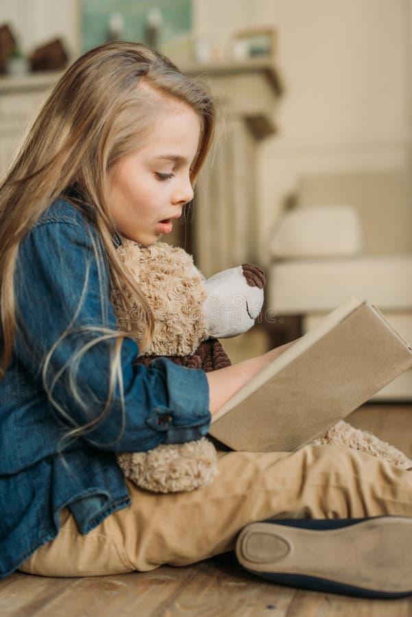 Opinião lateral a menina com o livro de leitura do urso de peluche imagem de stock royalty free