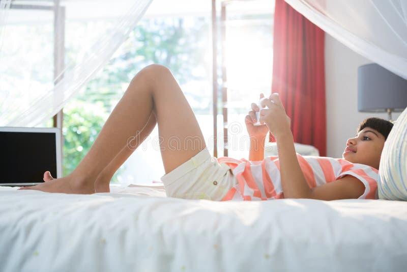 Opinião lateral a menina que usa o telefone celular na cama em casa imagem de stock