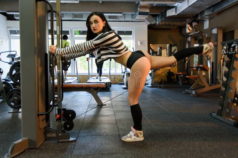 Opinião lateral a menina 'sexy' moreno da aptidão no desgaste branco e preto do esporte com o corpo perfeito que levanta no gym foto de stock