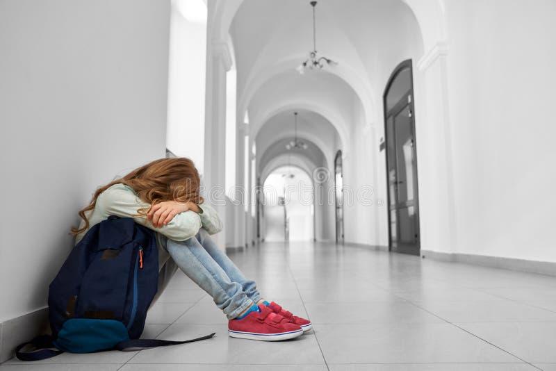 Opinião lateral a menina triste da escola que senta-se no assoalho fotos de stock