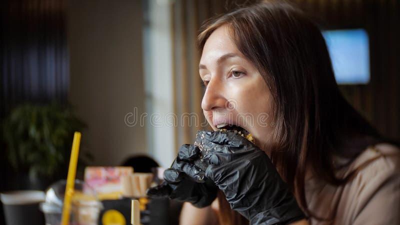 Opinião lateral a moça em luvas pretas que come um hamburguer no café imagem de stock