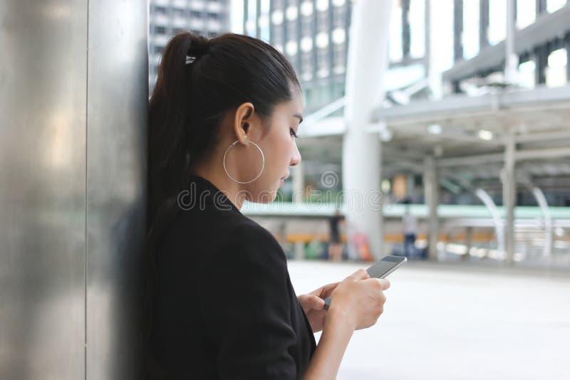 Opinião lateral a mulher asiática nova atrativa que guarda o telefone esperto móvel na rua da cidade Conceito social da rede foto de stock royalty free