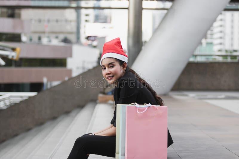 Opinião lateral a mulher asiática nova de sorriso com o chapéu de Santa e o saco de compras colorido que sentam-se fora após a co fotos de stock royalty free