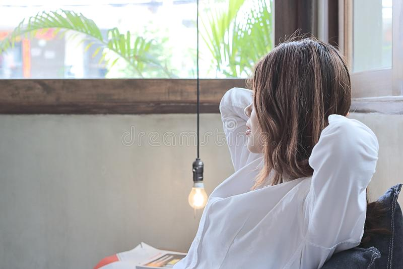 Opinião lateral a mulher asiática nova relaxado que senta e que olha longe dentro o fundo do espaço da cópia do aganinst da cafet fotografia de stock