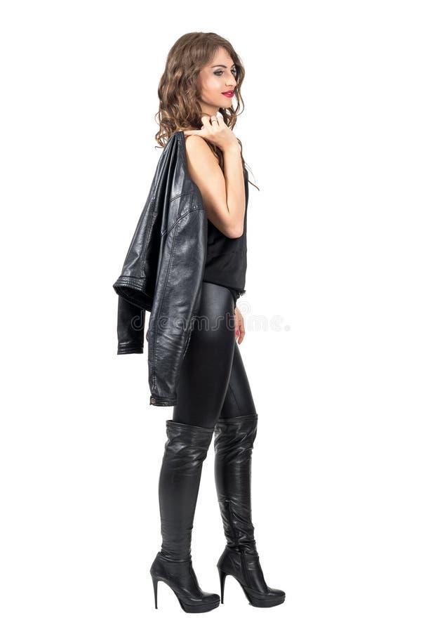 Opinião lateral a mulher bonita nova com cabelo encaracolado que anda e que olha pensativo afastado imagem de stock royalty free