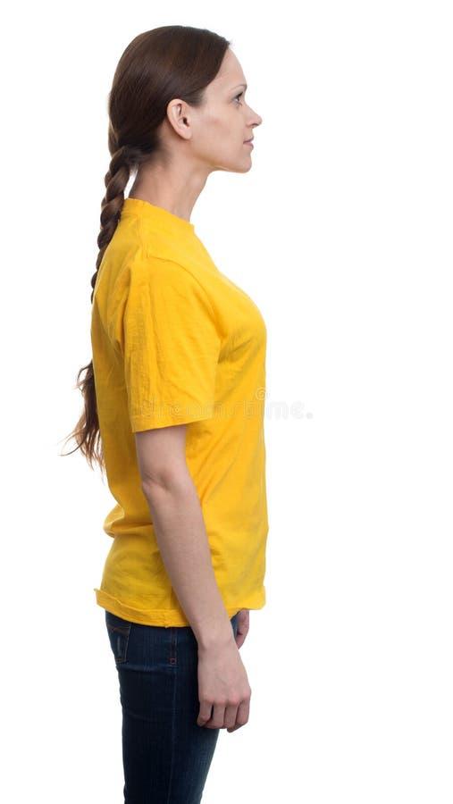 Opinião lateral a mulher bonita nova no t-shirt amarelo foto de stock royalty free