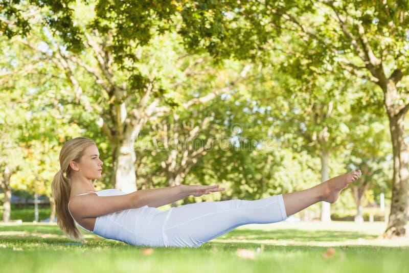 Opinião lateral a mulher bonita que faz a ioga em um parque fotografia de stock