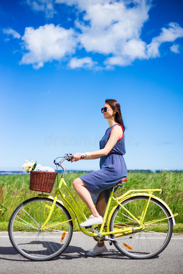 Opinião lateral a mulher bonita que monta a bicicleta retro no campo imagens de stock