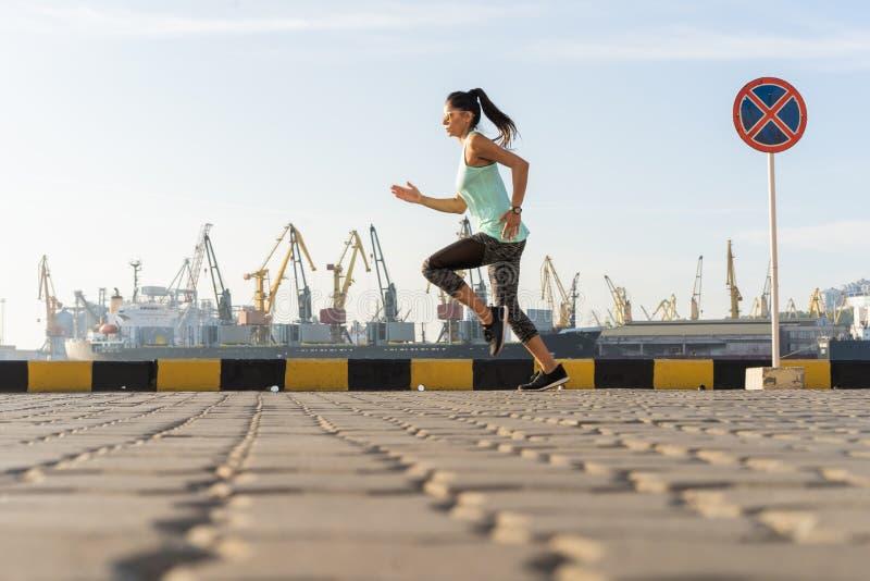 Opinião lateral a mulher da aptidão que corre em uma estrada pelo mar Treinamento do desportista no passeio do beira-mar no por d fotografia de stock