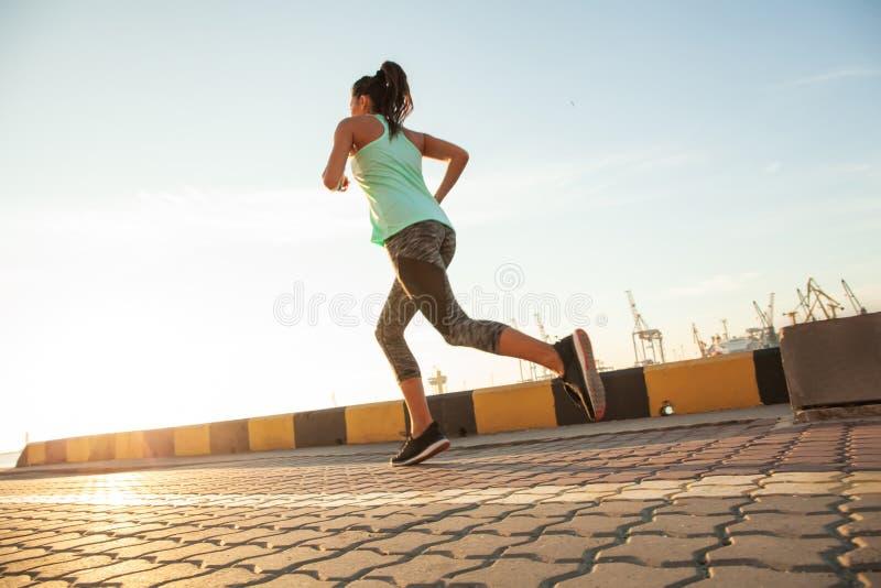 Opinião lateral a mulher da aptidão que corre em uma estrada pelo mar Treinamento do desportista no passeio do beira-mar no por d fotos de stock royalty free