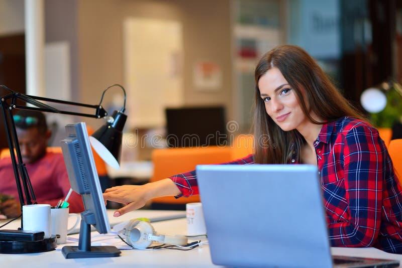 Opinião lateral a mulher de negócios feliz que trabalha em seu portátil no escritório foto de stock