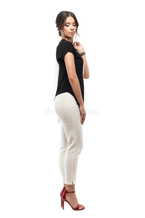 Opinião lateral a mulher de negócios nova no revestimento levando do terno e vista para baixo sobre o ombro imagens de stock royalty free