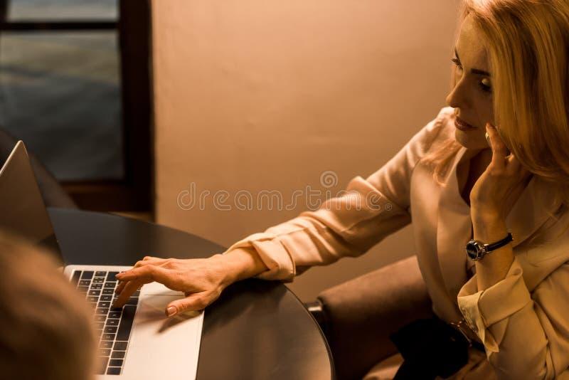 opinião lateral a mulher de negócios que fala no smartphone ao trabalhar no portátil imagem de stock royalty free