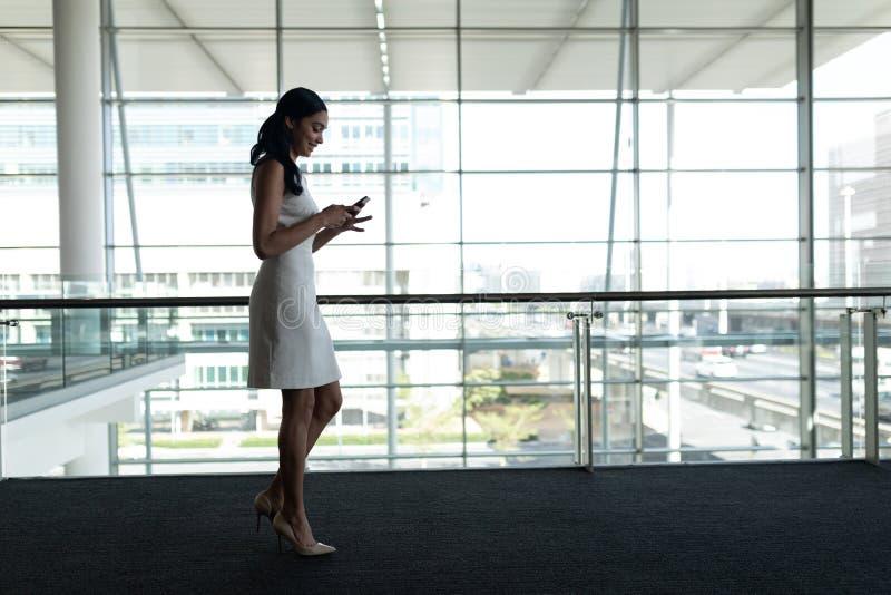 Opinião lateral a mulher de negócios que usa o telefone celular no escritório e andando em uma passagem do tapete imagens de stock