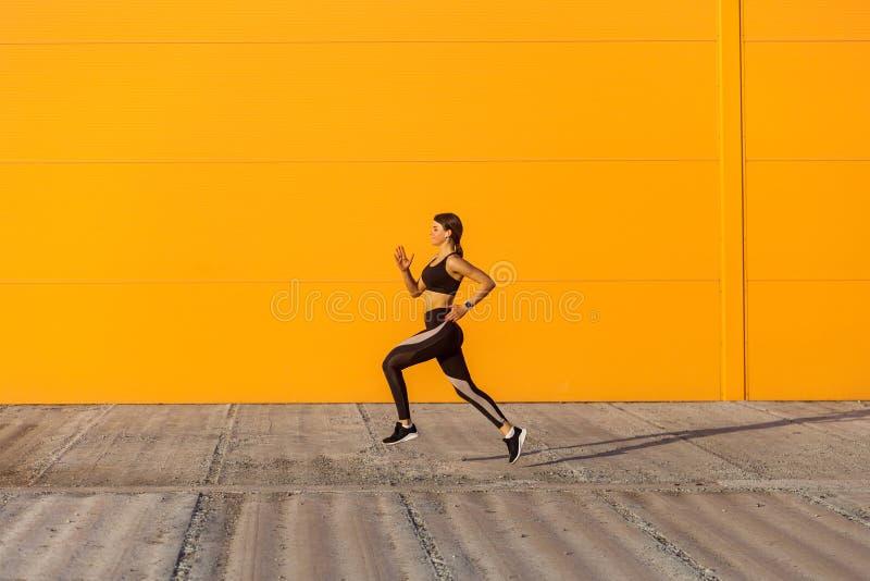 Opinião lateral a mulher desportiva atrativa nova que veste exercícios praticando do esporte do sporwear preto na manhã na rua, c fotos de stock royalty free