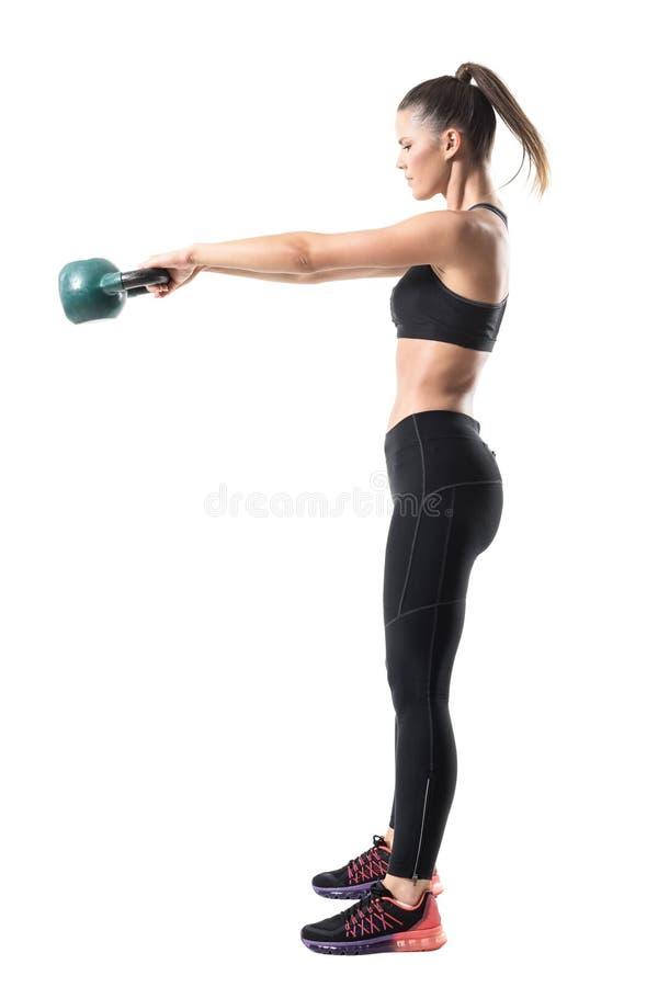 Opinião lateral a mulher desportiva forte da aptidão que balança 12 quilogramas de kettlebell no movimento do meio do ar fotos de stock