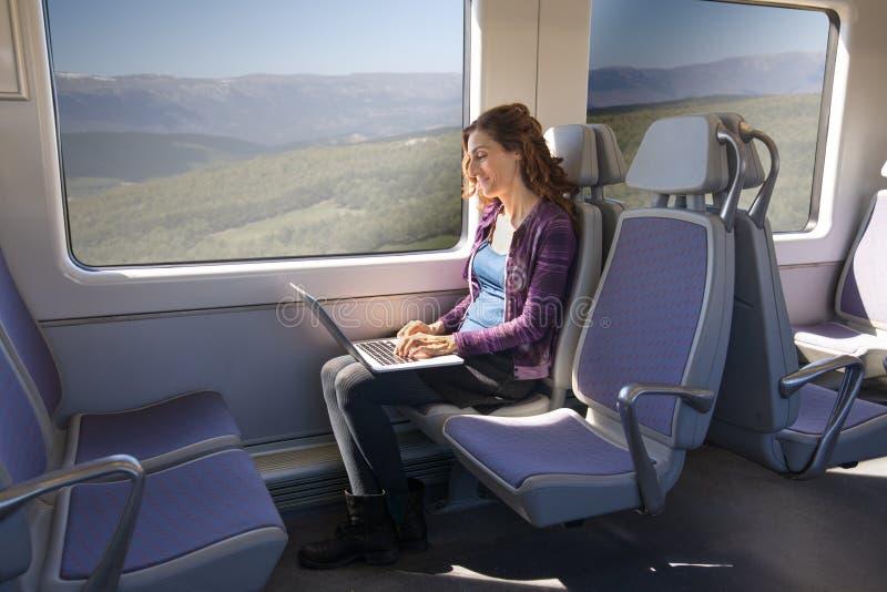 Opinião lateral a mulher no trem que datilografa no laptop foto de stock